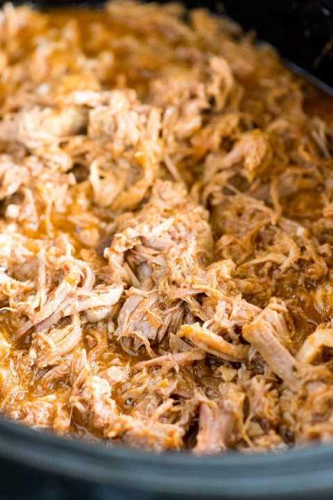 Primer del cerdo cocinado y desmenuzado en una olla de cocción lenta.