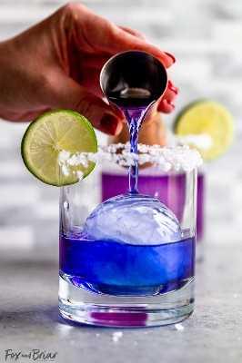 derramando tequila azul em um copo com gelo