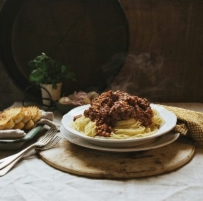 boloñesa servida en espagueti con albahaca, pan de ajo y ajo en el fondo