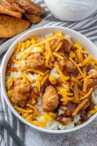 Foto aérea del tazón con papas, pollo, maíz, salsa y queso con gajos de papa