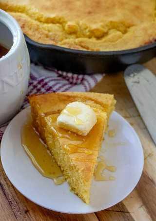 Rebanada terminada de pan de maíz en un plato con miel y mantequilla