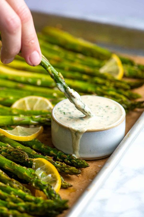 This roasted asparagus is a simple and quick accompaniment. The asparagus is perfectly tender with slightly crisp tips. Served with our five-minute garlic and herb sauce, it's deliciously garlicy, fresh, and vegetarian.