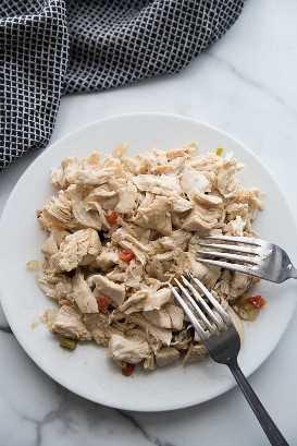 Um prato cheio de frango desfiado com dois garfos sobre ele.