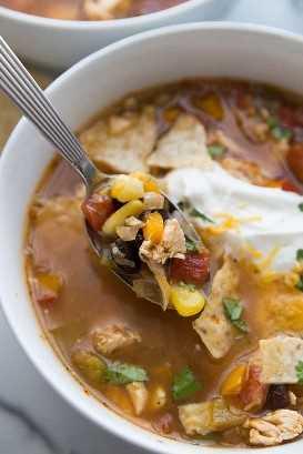 Uma colher de sopa de omelete de frango com pedaços de frango, milho, cenoura e tomate picado de uma tigela branca