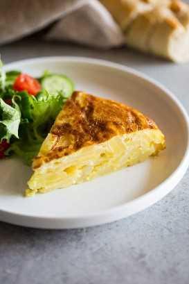 Una rebanada de tortilla de patata servida en un plato blanco con ensalada verde al lado y baguette en rodajas en el fondo.