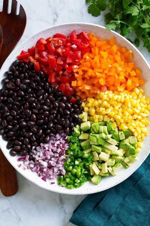 Ingredientes de ensalada de frijoles negros y maíz en un tazón antes de mezclar.