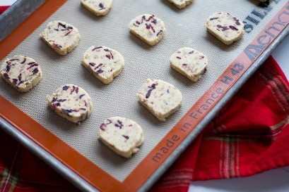 Bolinhos de manteiga alaranjados da porca do arando. Estes biscoitos fáceis de cortar e assar são aromatizados com raspas de laranja, baunilha, mirtilo e nozes. Eles são os biscoitos perfeitos para doar ou guardar para si!