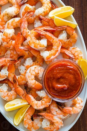 Perfectly baked shrimp on a serving platter with shrimp cocktail sauce