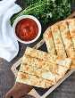 Essas palitos de alho e queijo são recheadas com alho, queijo e ervas para um paladar saboroso na pizza à noite. Também delicioso coberto com molho marinara!
