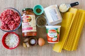 Ingredientes para lasaña con fideos de lasaña, salsa marinara, carne molida, queso ricotta, queso mozzarella y queso parmesano