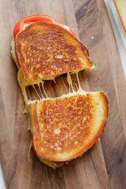 Sanduíche de queijo grelhado completo em uma placa de corte