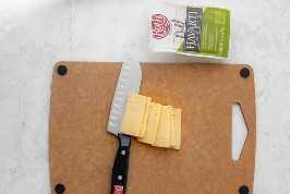 Corte o queijo Havarti em uma placa de corte