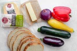 Ingredientes para fazer um sanduíche de queijo grelhado: pão, queijo Roth, manteiga e legumes variados.