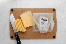 Corte o queijo Gouda em uma placa de corte