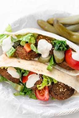 Sanduíche de falafel feito com molho de picles, tomate, salsa e tahine