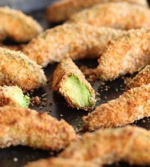 Batatas fritas de abacate recém-assadas, com foco em metade de uma batata frita mostrando o abacate