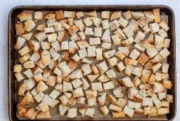 Cubos de pão torrado em uma assadeira