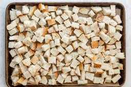 Cubos de pão em uma assadeira