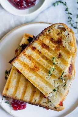 Resultado final da panini de peru mostrando duas metades do sanduíche empilhadas umas sobre as outras com um lado do molho de cranberry