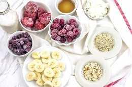 Bayas, plátanos, nueces y semillas en tazones para hacer batidos