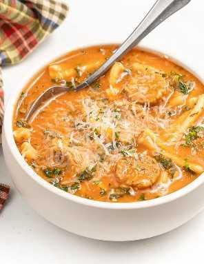 Uma tigela branca cheia de sopa de macarrão de salsicha italiana Vega com queijo parmesão vegan ralado por cima.