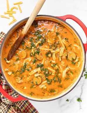 um grande pote vermelho de sopa de macarrão com linguiça vegana. Foto tirada de cima.