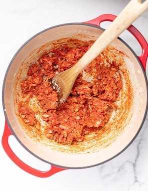 pasta de tomate e cebola em um forno vermelho holandês