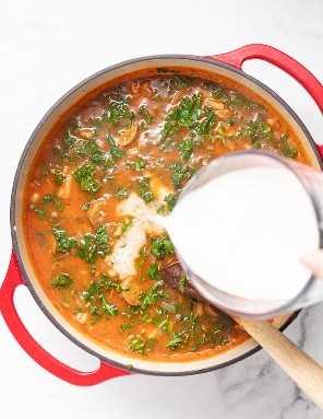 O leite de coco é derramado na sopa em um forno holandês