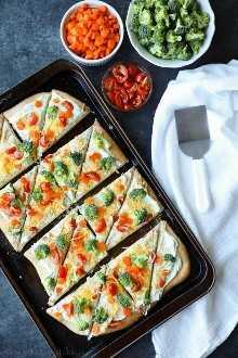 Esta pizza de vegetais fria é o melhor lanche de festa para as refeições de verão. Com uma crosta recém-assada, uma cobertura cremosa de rancho e legumes frescos, todos voltarão por segundos!