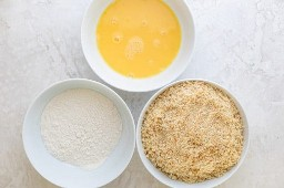 Três tigelas para dragar a berinjela: farinha, lavagem de ovos e farinha de rosca / azeite / parmesão