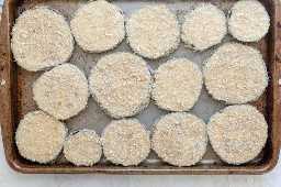 Fatias de berinjela após a dragagem da farinha, a lavagem dos ovos e a mistura de farinha de rosca prestes a assar