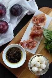 Ensalada de ciruela, mozzarella y prosciutto sobre zorro y brezo