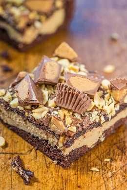Brownies de pastel de queso con taza de mantequilla de maní: brownies de chocolate con una capa de pastel de queso con mantequilla de maní y cubiertos con tazas de maní y mantequilla de maní. ¡Rico, decadente y sorprendente! ¡Una visita obligada para todos los amantes de la mantequilla de maní!