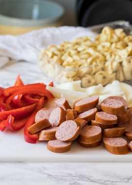 Esta receita fácil de jantar durante a semana começa com salsicha kielbasa, pimentão vermelho, cebola e macarrão tortellini gelado.