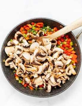 cogumelos picados crus em uma panela com outros legumes picados por baixo