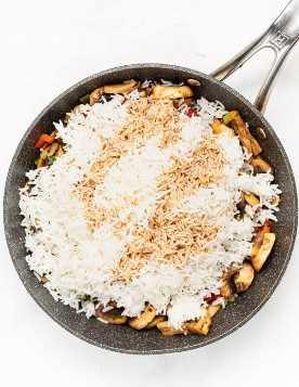 arroz branco em uma panela com legumes e molho de soja