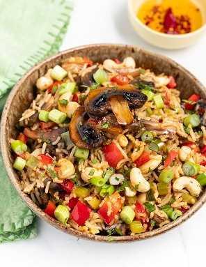 arroz frito com cogumelos em uma tigela com um guardanapo verde e uma tigela pequena de óleo de pimenta