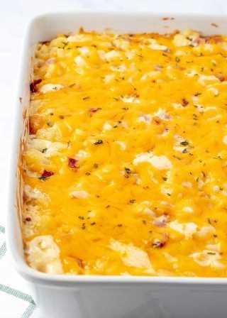 Papas con queso y jamón y tocino en una sartén con queso derretido encima