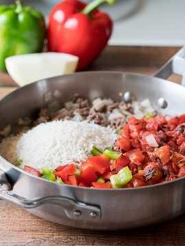 Dorar la hamburguesa en una sartén con un poco de cebolla, ajo y luego agregar los pimientos y tomates cortados en cubitos.