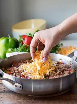 Cubra la carne molida cocida y el arroz con un poco de queso y agregue la tapa nuevamente hasta que el queso se derrita.