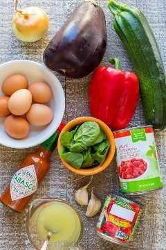 Esta sartén de brunch Ratatouille está cargada de calabacín, berenjenas abundantes y pimientos en salsa de tomate picante, coronada con huevo y espinacas frescas. El   natashaskitchen.com