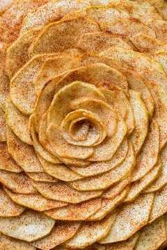 Esta torta de maçã é muito atraente! É coberto com um lindo padrão de maçã em fatias rosa (e é mais fácil do que você pensa!). Os sucos das fatias de maçã revestidas com canela e açúcar são cozidos na crosta suave e amanteigada. Esta torta de maçã e rosa é um pouco doce e completamente irresistível.