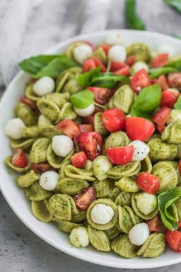 ¡El mejor plato de comida de verano, esta ensalada de pasta caprese está hecha con trozos de mozarella de perlas, jugosos tomates cherry y se mezcla con una salsa de pesto brillante!