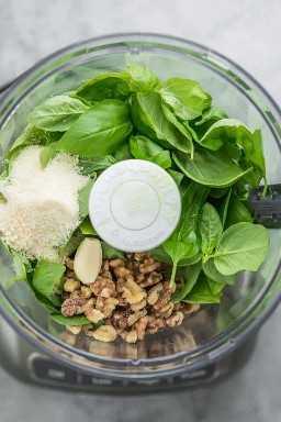 Procesador de alimentos con ingredientes para hacer pesto: albahaca, nueces, queso parmesano, ajo, aceite de oliva y jugo de limón.