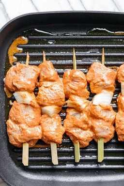 Plan de parrilla que muestra 5 brochetas de bambú con shish tawook y cebollas ensartadas y asadas