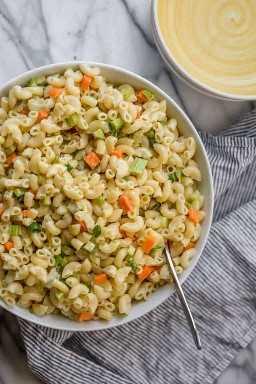 Tazón grande de ensalada de macarrones veganos que incluye pasta, zanahorias, apio, encurtidos, cebollas verdes y el aderezo.