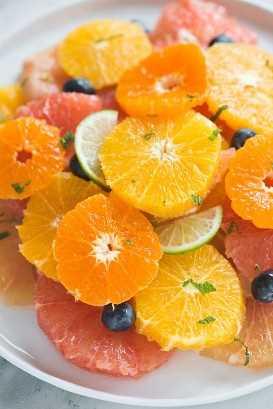 Anel de salada cítrica de fatias de laranja, toranja, tangerina, clementina e mirtilos em um prato branco.