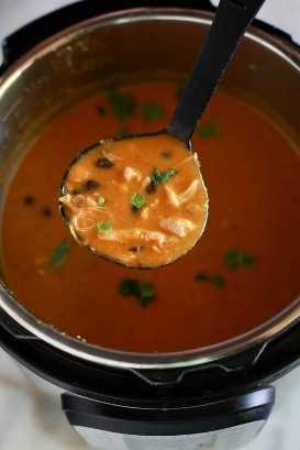 Uma panela instantânea cheia de sopa de enchilada de frango e uma concha que recolhe um pouco da sopa.