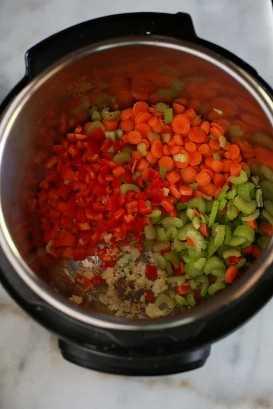 Legumes salteados em uma panela instantânea, como cenoura picada, pimentão, aipo, cebola e alho.
