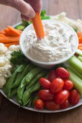 Um prato cheio de legumes variados com molho de vegetais no centro e alguém mergulhando uma cenoura no molho.